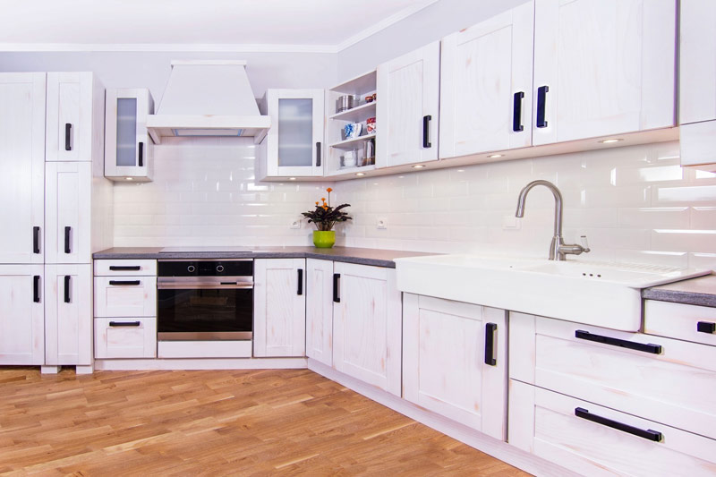 Pomalowane na biało meble z przecierką w kuchni inspirowanej stylem rustykalnym