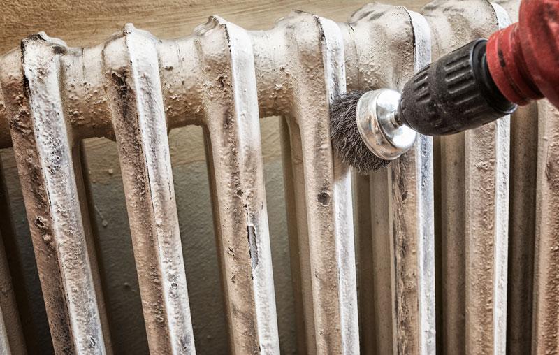 Oczyszczenie starego grzejnika przy pomocy szlifierki znacznie przyspiesza pracę.