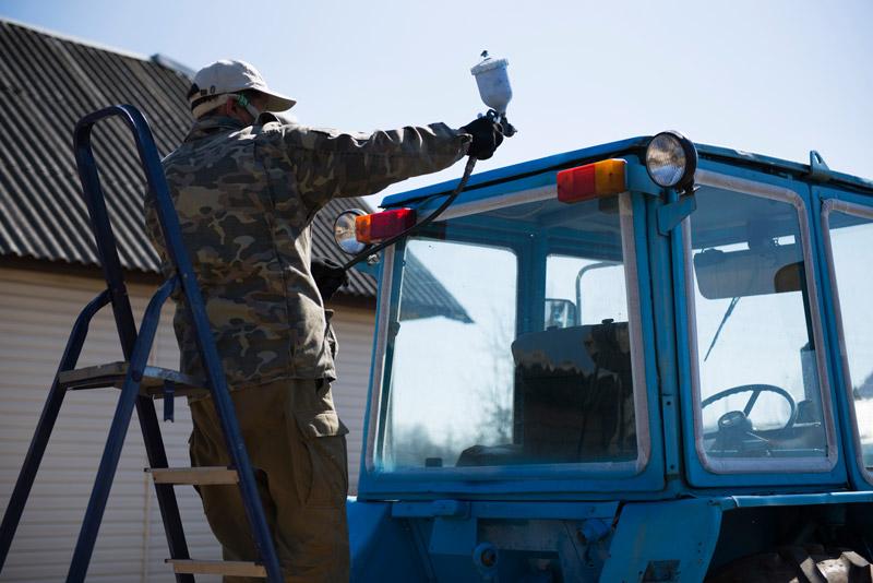Natryskowe malowanie traktora niebieską farbą do ciągników rolniczych.