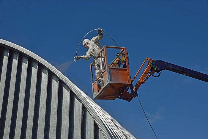 Mężczyzna na wysięgniku poddający renowacji dach z blachy.