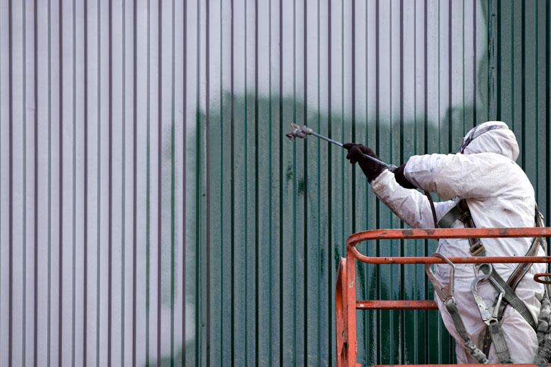 Malarz w białym kombinezonie stojący na podnośniku i malujący natryskowo stalową ścianę.
